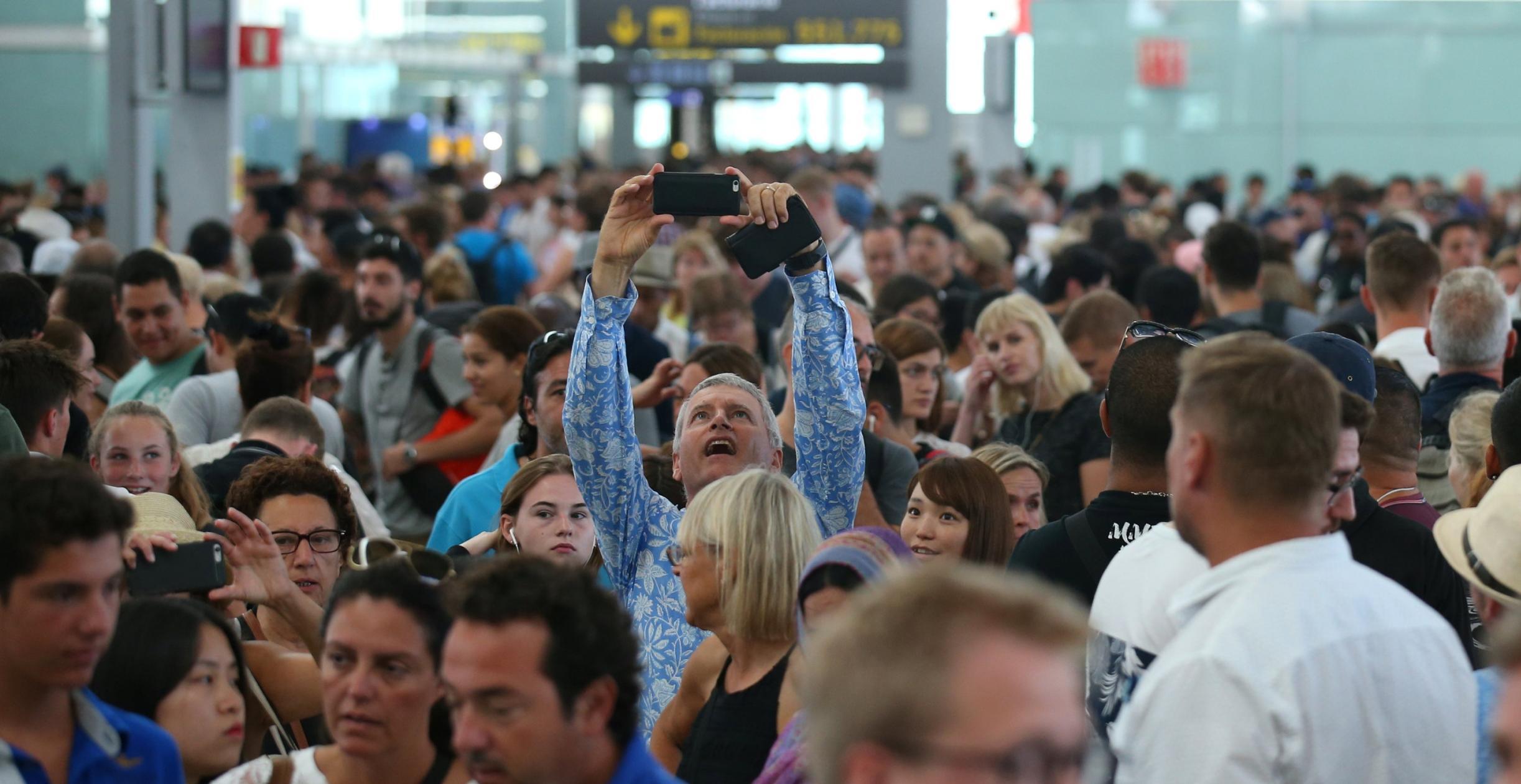 Un hombre toma una foto con su smartphone de las largas colas de pasajeros en los controles de seguridad del aeropuerto de Barcelona-El Prat, en la primera jornada de paros de los trabajadores de Eulen, encargada de este servicio. REUTERS/Albert Gea
