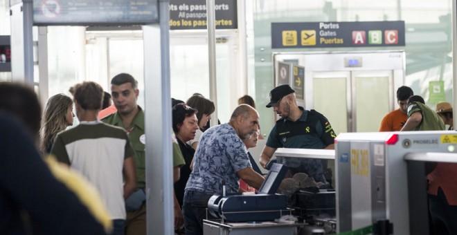 Efectivos de la Guardia Civil trabajan en los accesos a las puertas de embarque del aeropuerto de Barcelona-El Prat . EFE/Quique García