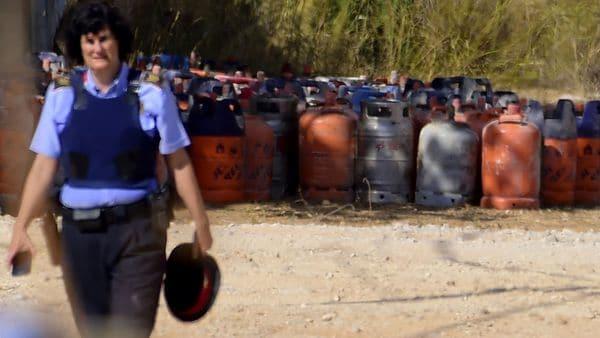 Una agente camina por las decenas de bombonas de gas halladas en el domicilio de Alcanar