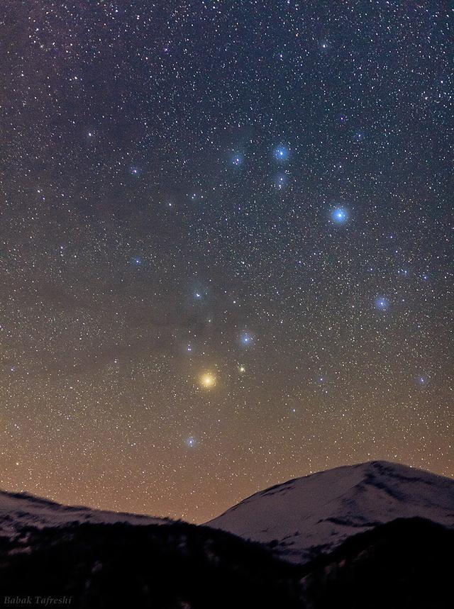 Antares, una supergigante roja en la constelación de Escorpio, brilla en un color anaranjado en el centro de esta imagen. Crédito: Babak Tafreshi/TWAN.