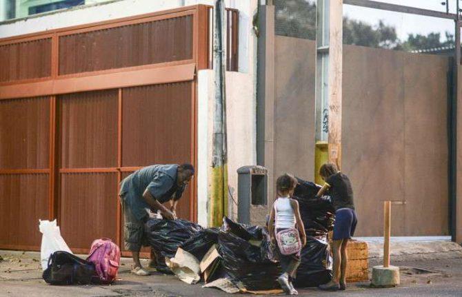 Un hombre junto a una niña busca comida en la basura en Caracas.