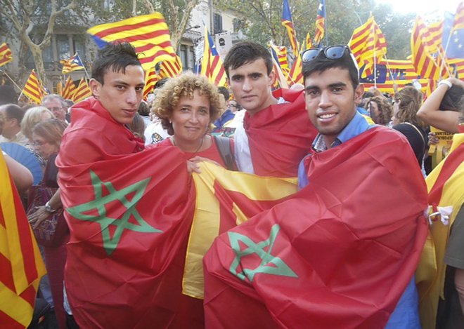 Marroquíes envueltos en banderas de su país y catalanas en una celebración de la Diada en Barcelona.