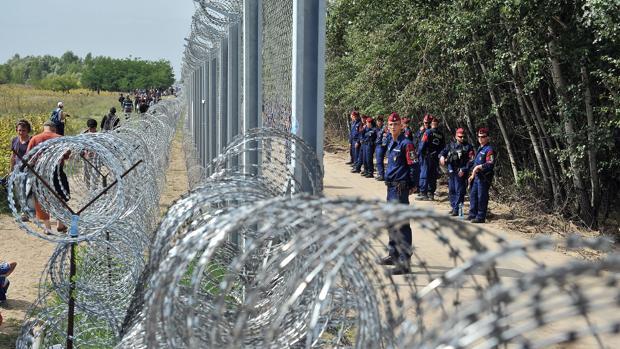 Un grupo de refugiados pasa frente al muro levantado por Hungría para impedir la llegada de inmigrantes